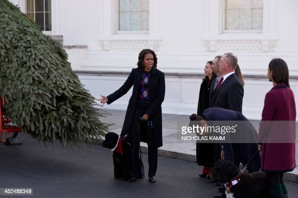 US First Lady Michelle Obama speaks to daughters Sasha and Maliawith dogs Sunny and Bo after receiving the White House Christmas tree in WashingtonDC...