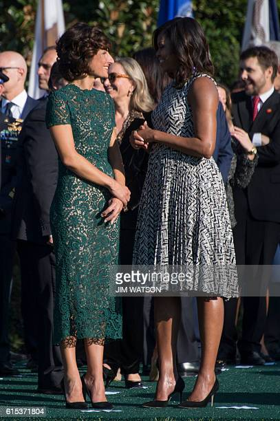 First Lady Michelle Obama speaks with the wife of Italian Prime Minister Matteo Renzi Mrs Agnese Landini during a state arrival ceremony at the White...