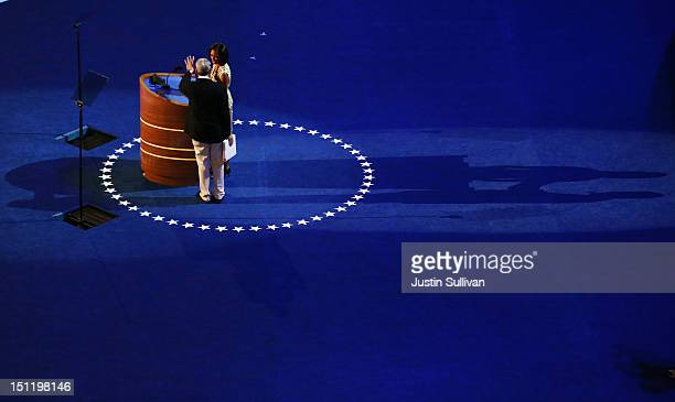 First lady Michelle Obama stands at the podium on stage with stage manager David Cove for a soundcheck during preparations for the Democratic...