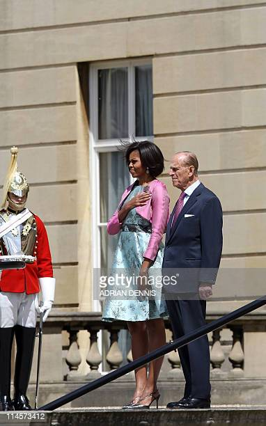 US First Lady Michelle Obama stands beside Britain's Prince Philip while the band play the US National Anthem at Buckingham Palace in London on May...