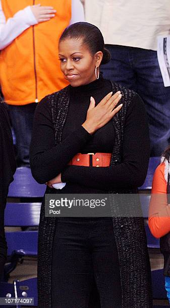 US first lady Michelle Obama stands for the National Anthem during a college basketball game at Howard University November 27 2010 in Washington DC...