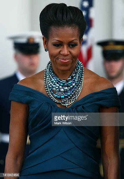 First lady Michelle Obama stands in the North Portico of the White House before attending a state dinner March 14 2012 in Washington DC Earlier in...