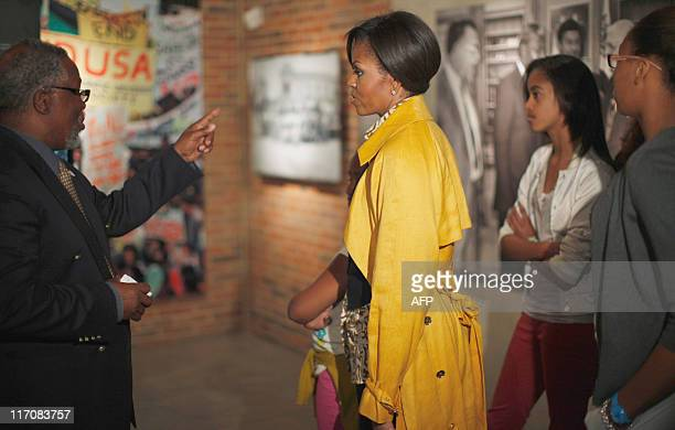 US first lady Michelle Obama stands with daughter Sasha obscured center and Malia as she visits the Apartheid Museum in Johannesburg South Africa on...