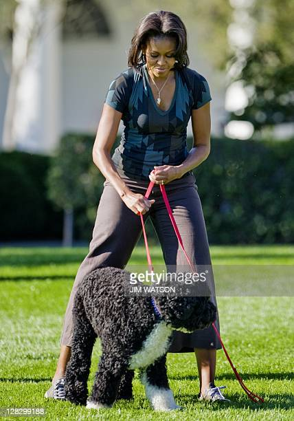 First Lady Michelle Obama stands with the family dog Bo as she hosts a Let's Move event on the South Lawn of the White House in Washington DC October...