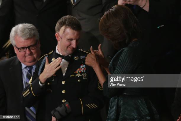 First lady Michelle Obama stands with US Army Ranger Sergeant First Class Cory Remsburg before US President Barack Obama delivers the State of the...
