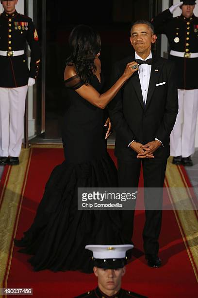 S First Lady Michelle Obama straightens US President Barack Obama's tie while they wait on the North Portico for the arrival of Chinese President Xi...