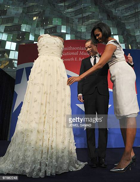 US First Lady Michelle Obama touches her 2009 inaugural gown as the designer of Mrs Obama�s inaugural dress Jason Wu looks on during a ceremony at...