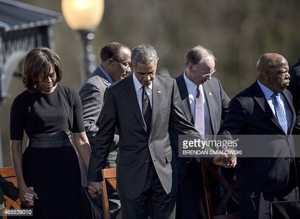 US First Lady Michelle Obama US President Barack Obama Robert J Bentley and US Representative John Lewis bow their heads for a prayer at the Edmund...