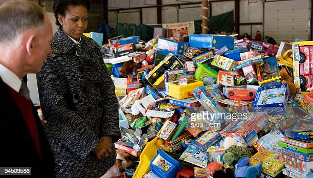 First Lady Michelle Obama walks alongside Toys for Tots Chief Executive Officer Pete Osman as she visits volunteers at the Toys for Tots warehouse in...