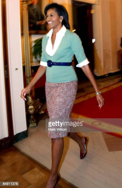 First Lady Michelle Obama walks into the East Room before an event at the White House on February 18 2009 in Washington DC Mrs Obama hosted an event...