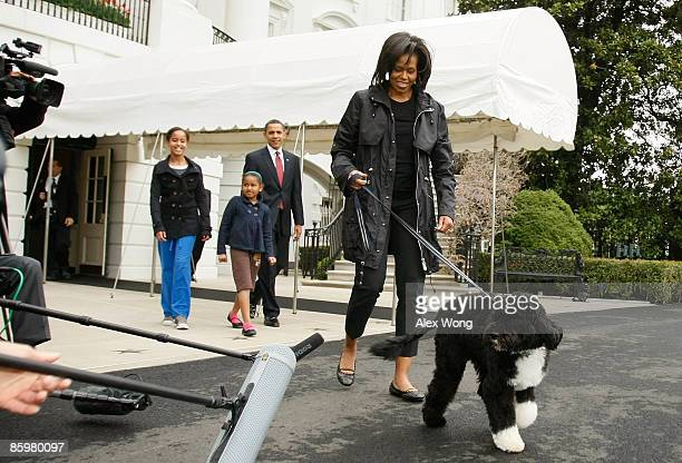 First lady Michelle Obama walks the family's new Portuguese water dog Bo followed by US President Barack Obama and their daughters Malia and Sasha...