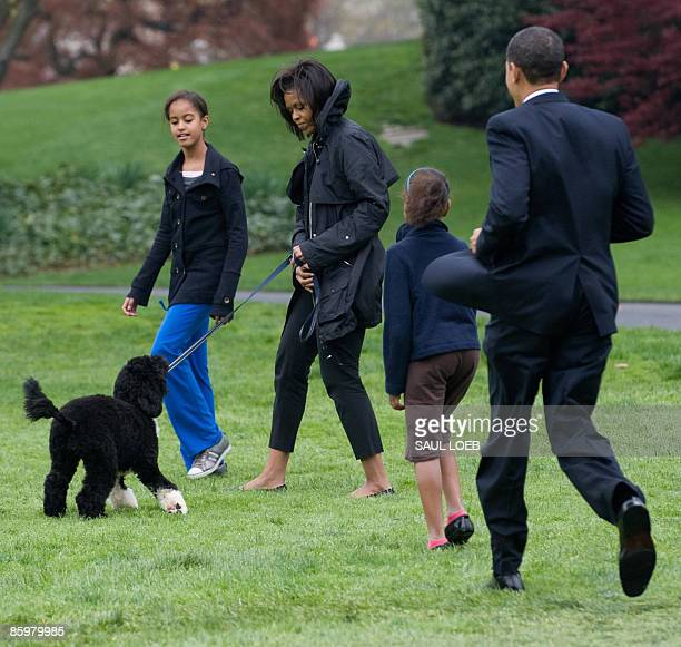 First Lady Michelle Obama walks the family's new sixmonth old Portuguese water dog Bo alongside daughters Malia and Sasha and US President Barack...