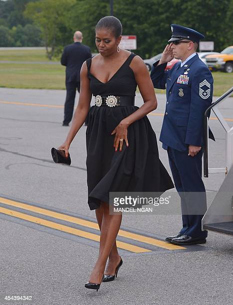 US First Lady Michelle Obama walks to a limousine upon arrival at Westchester County Airport in White Plains New York on August 30 2014 Obama is...