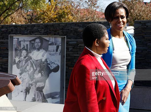US first lady Michelle Obama walks with Antoinette Sithole past a photo of her late brother Hector Pieterson was taken following his shooting after...
