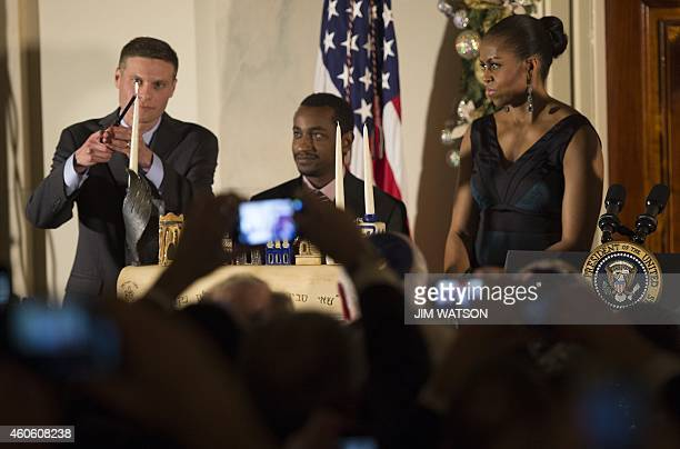 First Lady Michelle Obama watches as Dr Adam Levine Assistant Professor of Emergency Medicine at the Alpert Medical School at Brown University lights...