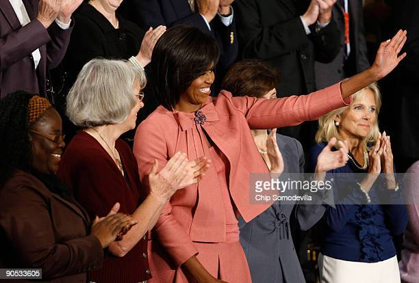 S first lady Michelle Obama waves as she arrives in the House chamber before US President Barack Obama addressed a joint session of the US Congress...