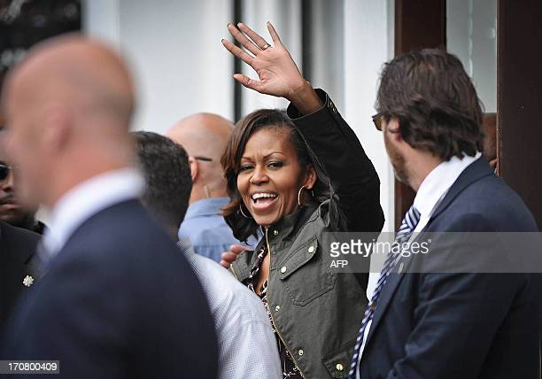 US First Lady Michelle Obama waves during a visit to Finnegans Pub in Dalkey in Ireland on June 18 2013 The US First Lady and her daughters visited...