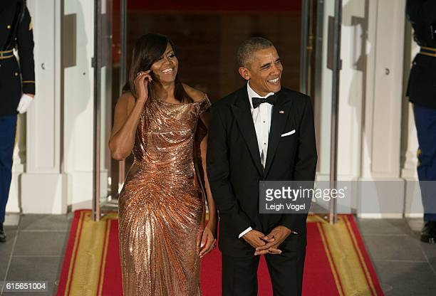 First Lady Michelle Obama wearing an Atelier Versace dress and President Barack Obama await the arrival of Italian Prime Minister Matteo Renzi and...