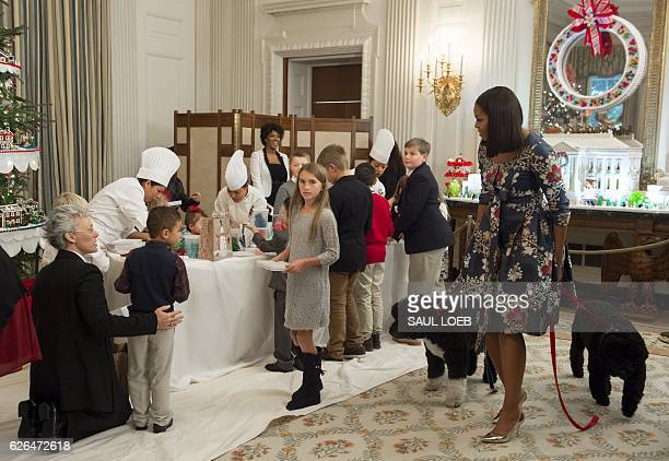First Lady Michelle Obama with the First Family's dogs Sunny and Bo greets children of military families as they make holiday crafts and treats...