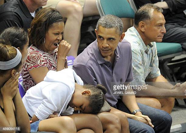 US First Lady Michelle Obama yawns as President Barack Obama and their daughters Sasha and Malia and other family members watch the Oregon State...