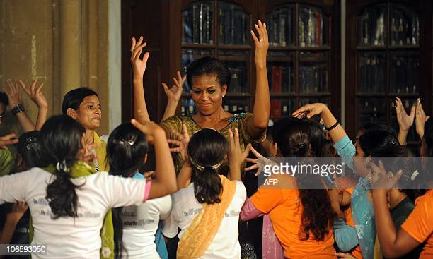 US First lady Mitchelle Obama dances to a Bollywood film song during an interaction with students from the Make A Difference NGO at the Mumbai...