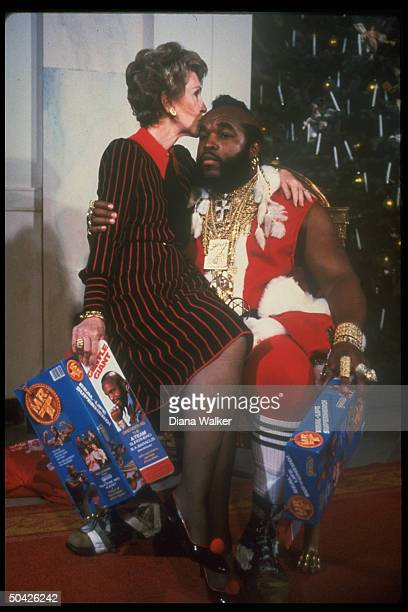 First lady Nancy Reagan sitting on lap kissing Mr T done up as Santa Clas at WH Christmas decoration tour