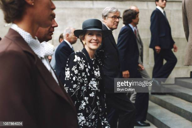 First Lady Nancy Reagan, wearing a black and white dress, matched with a black wide brimmed hat, pauses on the steps of St.Paul's Cathedral as she...