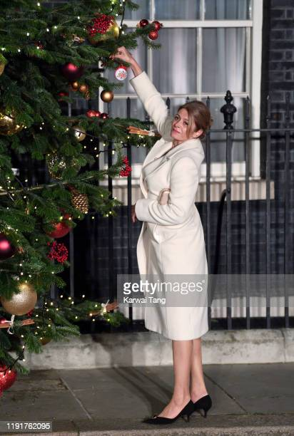 First Lady of Bulgaria Desislava Radeva, the wife of Bulgarian President Rumen Radev places a bauble on a Christmas tree as they arrive to attend a...