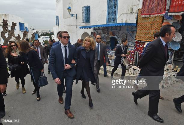 First Lady of France Brigitte Macron is escorted by a members of her personnel security detail during a visit to the town of Sidi Bou Said near Tunis...