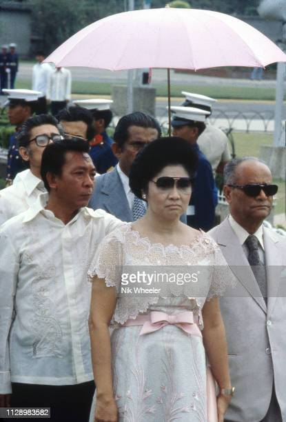 First Lady of the Philippines Imelda Marcos, wife of President Ferdinand Marcos, with her bodyguards in the rain in Manila.