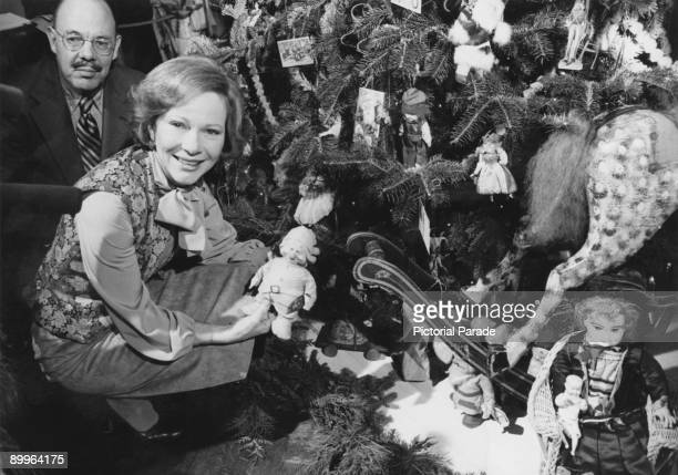 First Lady of the United States Rosalynn Carter holding a doll under the Christmas tree in the Blue Room at the White House Washington DC 12th...
