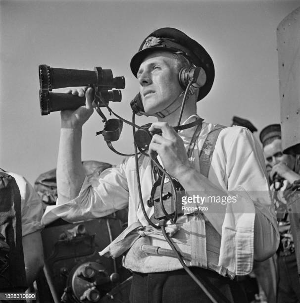 First Lieutenant Brian Longbottom , the ship's gun control officer, uses a pair of naval binoculars to watch for enemy aircraft aboard the Royal Navy...