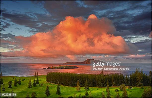 First light hits the coastal clouds and turns them a vivid pink at Slaughter bay, Norfolk Island.