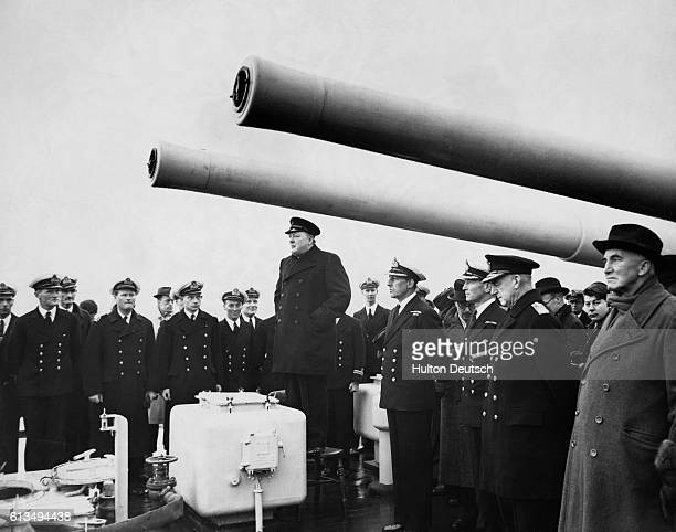 First Lord of the Admiralty Winston Churchill stands on a chair under two sixinch guns to address the crew of the HMS Exeter upon its return to...