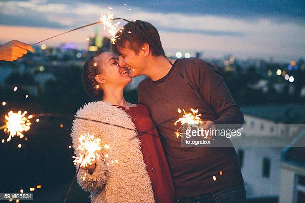 first love: young adult couple kiss in front of sparklers - teenage couple stock photos and pictures