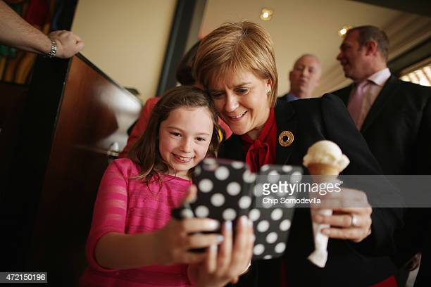 First Minister and leader of the Scottish National Party Nicola Sturgeon poses for a 'selfie' with a girl after buying an ice cream cone Cafe Nardini...