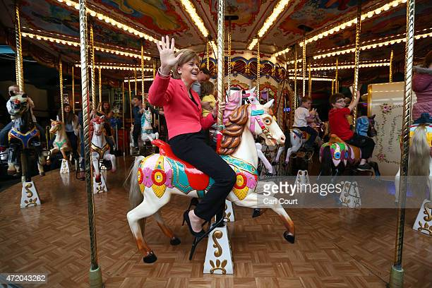 First Minister and leader of the SNP Nicola Sturgeon rides a carousel during a visit to a theme park while campaigning on May 3 2015 in Motherwell...