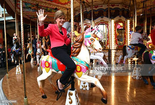 First Minister and leader of the SNP Nicola Sturgeon waves as she rides a carousel during a visit to a theme park while campaigning on May 3 2015 in...