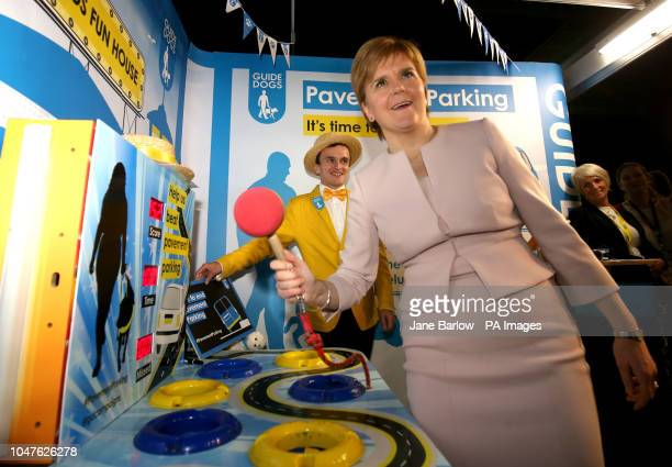 First Minister Nicola Sturgeon plays a 'whackamole' game at the Guide Dogs trade stand part of the charity's campaign against pavement parking at the...
