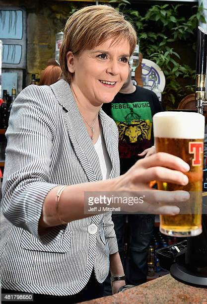 First Minister Nicola Sturgeon pulls a pint of lager as she joins invited guests attend the reopening of the Clutha Bar on July 24 2015 in Glasgow...