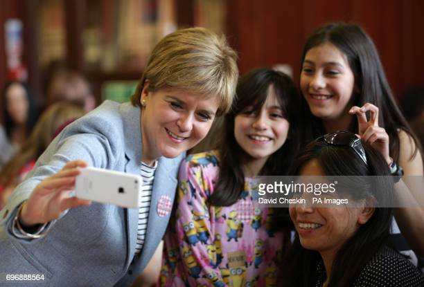 First Minister Nicola Sturgeon takes a photograph as she joins people at Glasgow Women's Library as she attends a tea party which is one of more than...