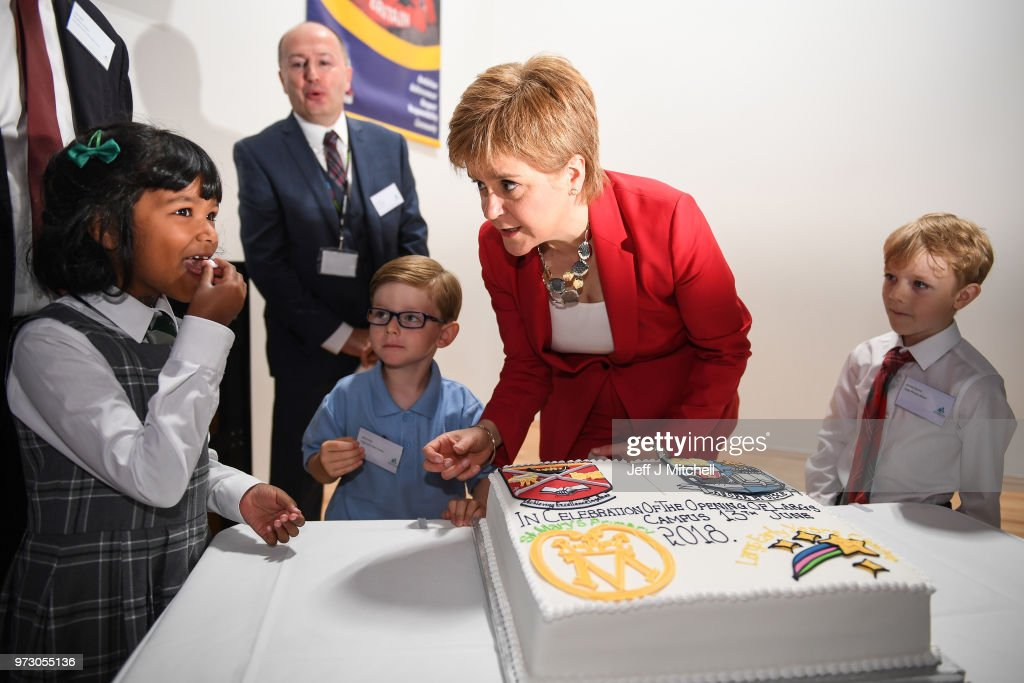 First Minister Nicola Sturgeon watches a young student after cutting a celebratory cake as she opens the new Largs Campus school building on June 13, 2018 in Largs,Scotland. The new Largs Campus, which has been part-funded by the Scottish Government's Schools for the Future campaign, provides a home for an early years centre, Largs Primary, St Mary's Primary and Largs Academy.