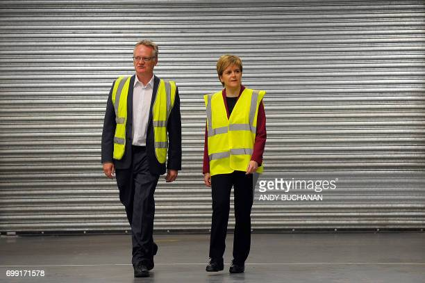 First Minister of Scotland Nicola Sturgeon is shown around by manager John Reid during a visit to the Michelin Tyre factory in Dundee Scotland on...