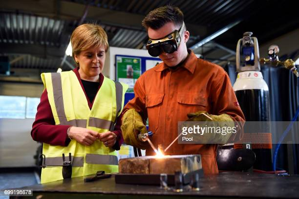 First Minister of Scotland Nicola Sturgeon watches an apprentice work during a visit to the Michelin Tyre factory on June 21 2017 in Dundee Scotland...