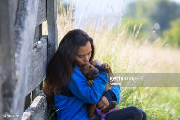First Nation Canadian woman plays with her pet dog