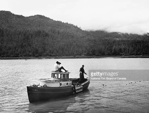 A First Nations fisherman drags a seine net on the Lower Skeena River while a photographer from the National Film Board of Canada takes pictures...