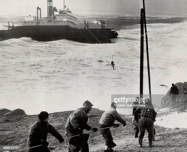 First of the crew of 31 is seen being rescued by coast guard breeches buoy as high winds and turbulent seas beat the stricken and battered collier...