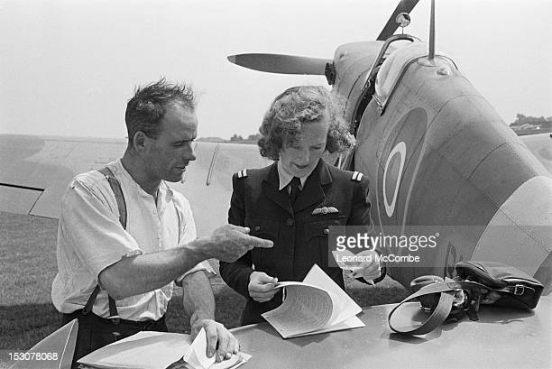 First Officer Faith Bennett of the ATA signing a collection chit for a Supermarine Spitfire fighter at a factory airfield in Britain September 1944...