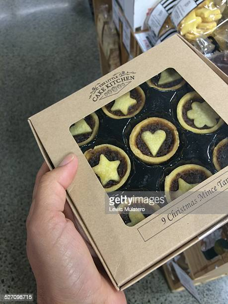 First person POV of of hand holding a box of mini mince pies in a shop