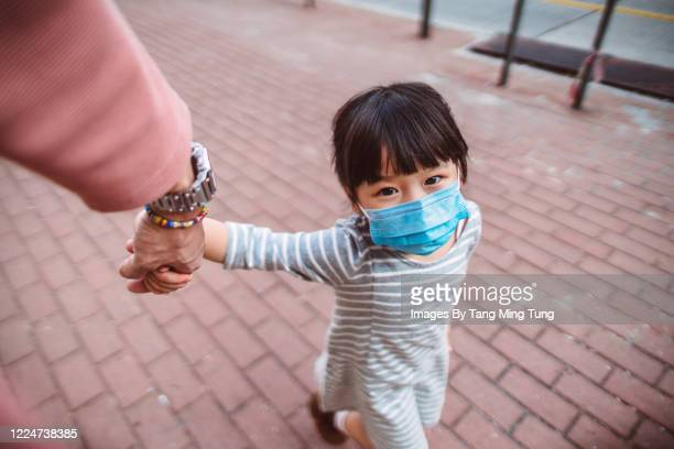 first person perspective of dad holding little daughter's hand who's wearing a medical face mask while they strolling on the street joyfully. - genderblend stock pictures, royalty-free photos & images